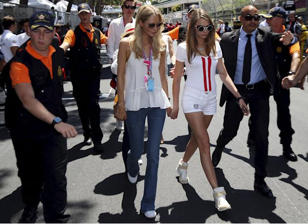 British model Cara Delevingne and her sister Poppy Delevingne arrive at the starting grid before the Monaco F1 Grand Prix