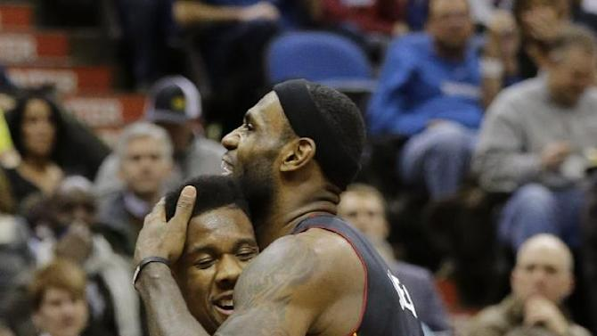 Miami Heat forward LeBron James, right, hugs guard Norris Cole, left, during the second quarter of an NBA basketball game against the Minnesota Timberwolves in Minneapolis, Saturday, Dec. 7, 2013. James had a game-high 21 points as the Heat won 103-82