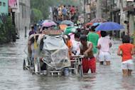 Residents wade through a flooded street in the town of Navotas in suburban Manila on August 2, 2012, after heavy rains and strong winds were brought about by Typhoon Saola. Saola induced widespread flooding across the northern Philippines this week that claimed at least 37 lives according to the government's updated toll