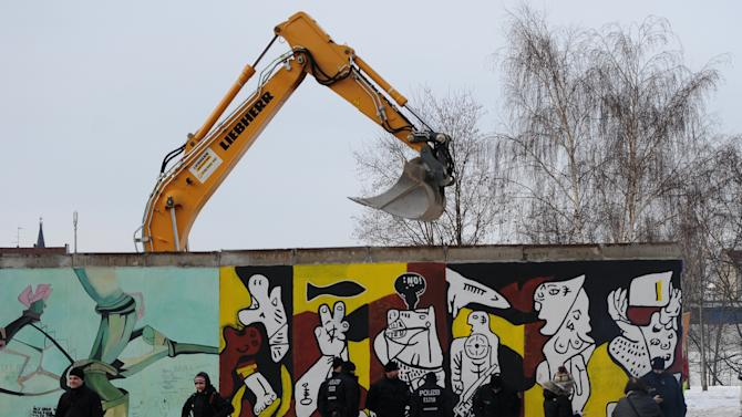 Police officers guard a construction site and sections of the East Side Gallery, while parts of the former Berlin Wall are removed in Berlin, Germany, Wednesday March 27, 2013. Work crews backed by about 250 police have removed portions of the Berlin Wall known as the East Side Gallery to make way for an upscale building project, despite demands by protesters that the site be preserved. Plans to remove part of the 1.3-kilometer (3/4-mile) stretch of wall sparked protests that developers were sacrificing history for profit. (AP Photo/dpa, Britta Pedersen)