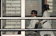 Chinese activist activist Chen Guangcheng (L) is seen in a wheelchair pushed by a nurse at the Chaoyang hospital in Beijing on May 2. The dissident at the center of a standoff between Beijing and Washington on Tuesday accused Chinese authorities of a pattern of abuse against his family as he again took his case to US lawmakers