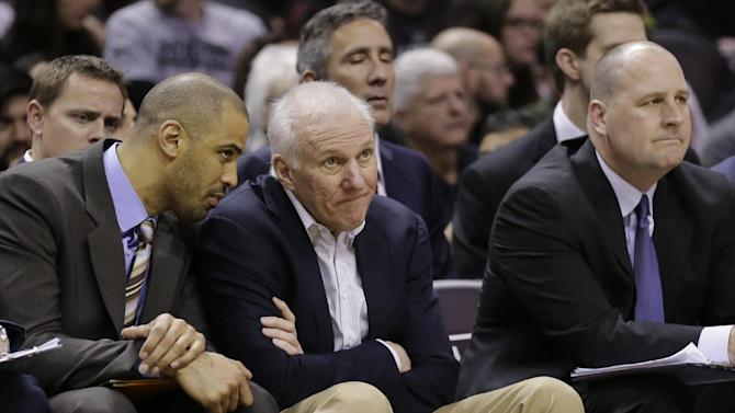 San Antonio Spurs coach Gregg Popovich, center, sits with assistant coaches Ime Udoka, left, and Jim Boylen, right, during the second half of an NBA basketball game against the Milwaukee Bucks, Sunday, Jan. 19, 2014, in San Antonio. San Antonio won 110-82