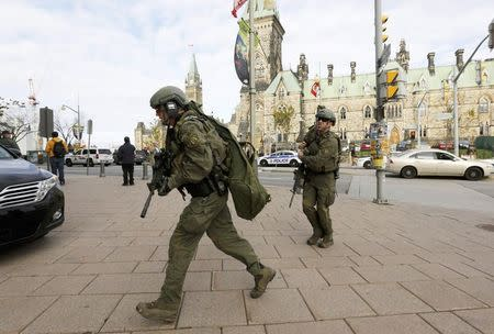 Armed RCMP officers head towards the Langevin Block on Parliament Hilll following a shooting incident in Ottawa