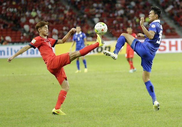 Singapore's Gabriel Quak Jun Yi, left, and Thailand's Adisak Kraisorn compete for the ball during their AFF Suzuki Cup Group B soccer match in Singapore, Sunday, Nov. 23, 2014.(AP Photo/Wong Maye-E)
