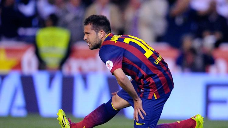 Barcelona's Jordi Alba grimaces while holding his leg during the final of the Copa del Rey between FC Barcelona and Real Madrid at the Mestalla stadium in Valencia, Spain, Wednesday, April 16, 2014