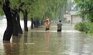 Image provided by North Korea's official Korean Central News Agency shows people walking down a flooded road in Anju city in North Korea's South Phongan province. A United Nations team will visit flood-hit areas of North Korea to consider possible aid, a UN official said on Tuesday after Pyongyang reported scores dead and tens of thousands homeless