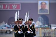 "Honor guards are seen marching during a daily flag-lowering ceremony in Beijing, on March 6, 2013. China's newly-installed president Xi Jinping has close ties to the country's expanding military and on Sunday called for the armed forces to strengthen their ability to ""win battles."""