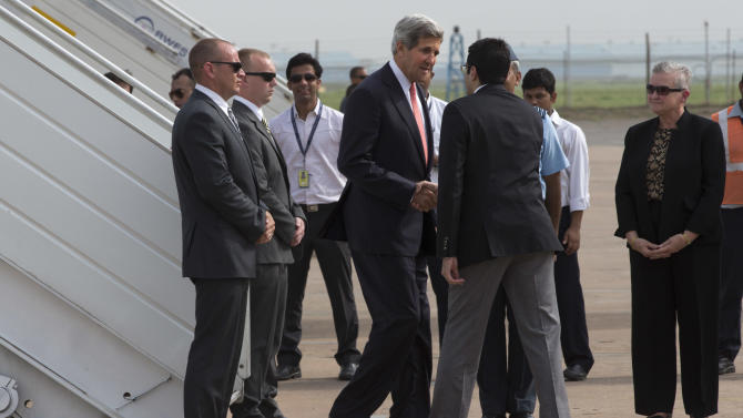 U.S. Secretary of State John Kerry, center left, is greeted by Aman Puri, with the Indian protocol office, upon arrival in New Delhi, India on Sunday, June 23, 2013, on his first visit to India as secretary. At right is U.S. Ambassador to India Nancy Powell. (AP Photo/Jacquelyn Martin, Pool)