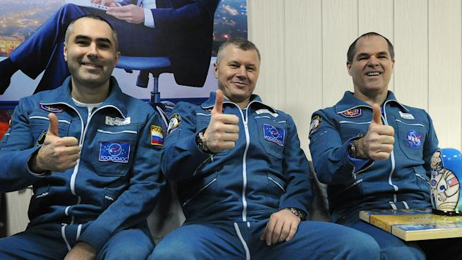 Russian cosmonauts Yevgeny Tarelkin, left, Oleg Novitsky, center, and NASA's astronaut Kevin Ford pose for a photo at the airport of the Kazakh city of Kostanai after their landing in northern Kazakhstan, Saturday, March 16, 2013. A Soyuz space capsule carrying a Russian-American crew members landed Saturday morning on the steppes of Kazakhstan, safely returning the three men to Earth after a 144-day mission to the International Space Station. The crew members had been scheduled to return on Friday, but the landing was postponed by a day because of bad weather. (AP Photo/Alexander Nemenov, Pool)