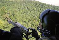 This file photo shows a Philippine Air Force gunner manning a machine gun as a helicopter flies over an area in restive southern Philippines, in 2008. A new video has emerged of an Australian kidnapped by suspected Muslim extremists in the Philippines, with the foreign office on Monday saying it proved he was still alive in late March
