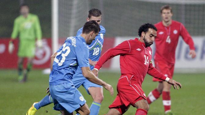 Slovenia's Dalibor Stevanovic, left, is challenged by Canada's Dwayne De Rosario during a friendly soccer match between Slovenia and Canada, in Celje, Slovenia, Tuesday, Nov. 19, 2013