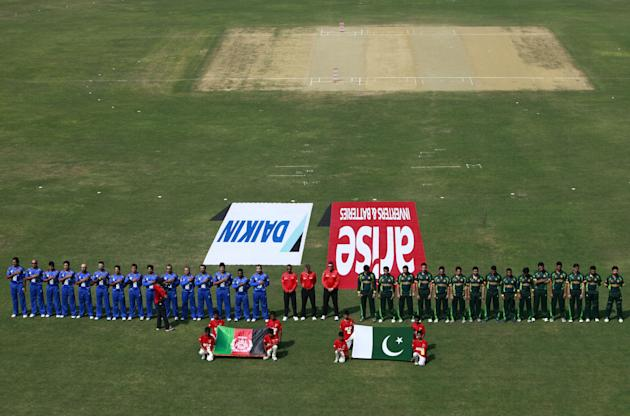 Afghanistan players, left, and Pakistan players, right, stand for the national anthem before their match in the Asia Cup one-day international cricket tournament in Fatullah, near Dhaka, Bangladesh, T