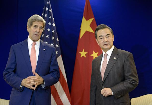 China's Foreign Minister Wang Yi, right, listens while U.S. Secretary of State John Kerry talks before a bilateral meeting at the Putra World Trade Center in Kuala Lumpur, Malaysia Wednesday, Aug. 5,