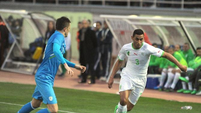 In this photo dated Wednesday, March 5, 2014, Algerian player, Ghoulam Faouzi Ghoulam, right, controls the ball while an unidentified Slovenian player looks on during their friendly soccer match at Blida stadium, near the Algerian capital Algiers. Algeria defeated Slovenia 2-0
