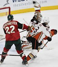 Anaheim Ducks' goalie John Gibson, center, makes a glove save on a shot as Ducks' Shea Theodore, right defends against Minnesota Wild's Nino Niederreiter (22), of Switzerland, in the first period of an NHL hockey game, Tuesday, Feb. 14, 2017, in St. Paul, Minn. (AP Photo/Tom Olmscheid)