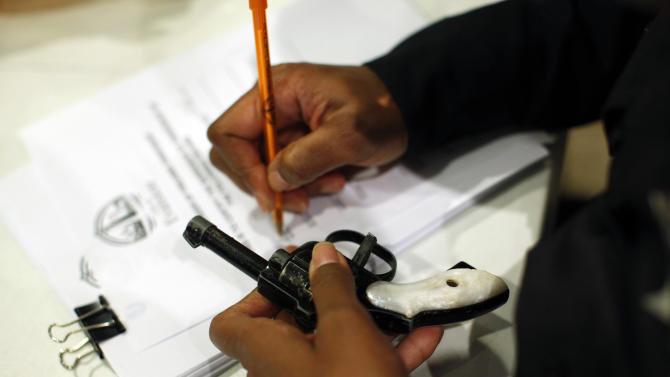 Evanston police officer documents some information on a firearm that was turned in as part of an amnesty-based gun buyback program in Evanston, Illinois