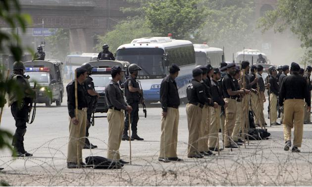 The buses transporting the Pakistan and Zimbabwe cricket teams arrive at Gaddafi stadium under armed escort before the start of the final cricket match of their series in Lahore