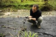 Suren Gazaryan looks at a black substance close to the Sochi 2014 Winter Olympics site. He says the substance is a mudslide from an illegal dump