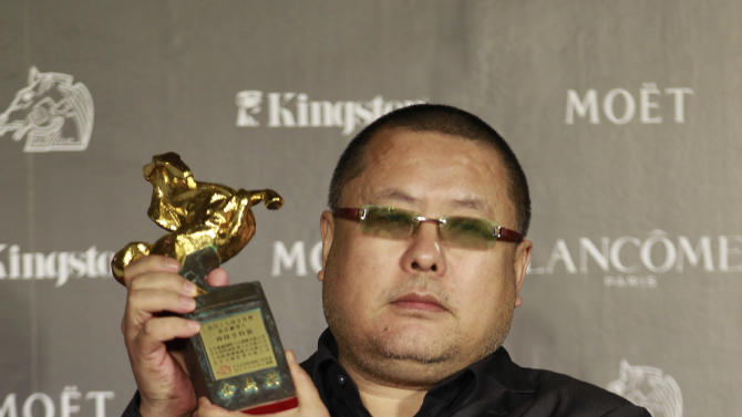"""Chinese director Gao QunShu holds his award for the Best Feature Film for the film """"Beijing Blues"""" at the 49th Golden Horse Awards at the Luodong Cultural Working House in Yilan County, Taiwan, Saturday, Nov. 24, 2012. The Golden Horse awards are one of  the Chinese-language film industry's biggest annual events. (AP Photo/Chiang Ying-ying)"""