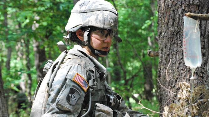 In a May 9, 2012 photo, Capt. Sara Rodriguez of the 101st Airborne Division inserts an IV line during the expert field medical badge testing at Fort Campbell, Ky. Female soldiers are moving into new jobs in once all-male units as the U.S. Army breaks down formal barriers in recognition of what's already happened in wars in Iraq and Afghanistan.   (AP Photo/Kristin M. Hall)