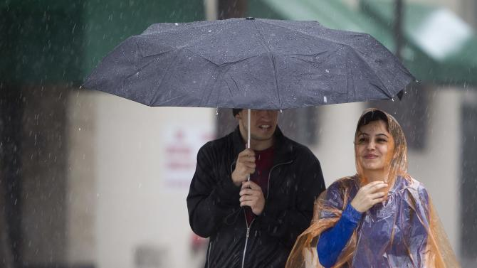 People walk in the heavy rain along Biscayne Blvd in Miami
