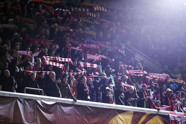 Liverpool fans hold up their football scarves and sing 'You'll Never Walk Alone' before the UEFA Europa League round of 32 football match between Liverpool and Besiktas in Liverpool on Feb