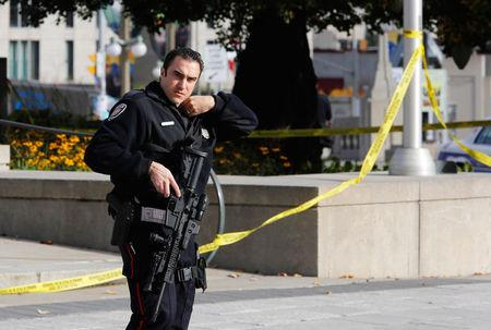 A police officer patrols the scene near the Canada War Memorial following a shooting incident in Ottawa