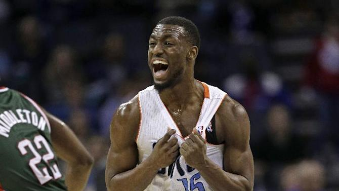 Charlotte Bobcats' Kemba Walker (15) reacts after making a 3-point shot against the Milwaukee Bucks during the second half of an NBA basketball game in Charlotte, N.C., Monday, Dec. 23, 2013. The Bobcats won 111-110 in overtime