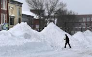 A man crosses Maine Street where snow has been piled high during a blizzard, Monday, Feb. 13, 2017, in Brunswick, Maine. A fluffy snow up to two-feet deep blanketed parts of the Northeast, just days after the biggest storm of the season dumped up to 19 inches of snow on the region. (AP Photo/Robert F. Bukaty)