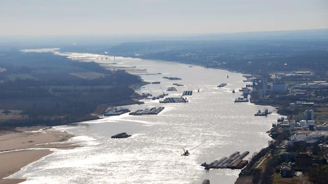 FILE - This Dec. 5, 2012 file photo provided by The United States Coast Guard shows barges passing in tight quarters due to low water levels as they navigate the Mississippi River near St. Louis. The Mississippi River, so low for much of the winter that barge traffic was nearly halted, could reach up to 10 feet above flood stage by the middle of next week in parts of Iowa, Illinois and Missouri, National Weather Service hydrologists said Wednesday, April 17, 2013. (AP Photo/United States Coast Guard, Colby Buchanan)