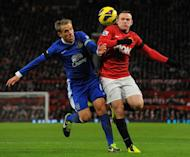 Everton's English defender Phil Neville (L) tangles with Manchester United's English striker Wayne Rooney (R) during the English Premier League football match between Manchester United and Everton at Old Trafford, Manchester, North West England, on February 10, 2013. United won 2-0