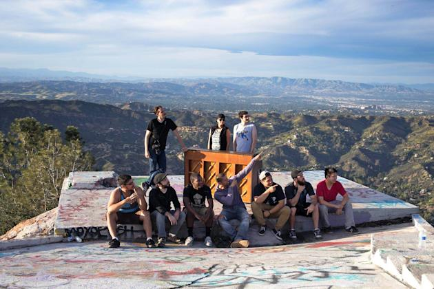 In this March, 2015 photo, members of a music video crew pose at Topanga Lookout in the Santa Monica Mountains with an upright piano they hauled up there in Calabasas, Calif. For a couple of days this