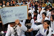 An Indian demonstrator holds a placard as others shout slogans during a protest calling for better safety for women following the rape of a student in New Delhi on December 24, 2012. Indian Prime Minister Manmohan Singh has appealed for calm and vowed to protect women as police struggled to quell increasing outrage over sex crimes following the gang-rape of a student