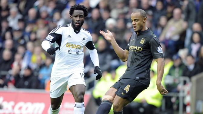 Swansea City's Wilfried Bony challenges Manchester City's Vincent Company during their English Premier League soccer match at the Liberty Stadium in Swansea