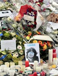 A picture of French late cartoonist Jean Cabut aka Cabu, flowers, candles and pens are placed at the entrance of the French weekly newspaper Charlie Hebdo's editorial office, on January 9, 2015