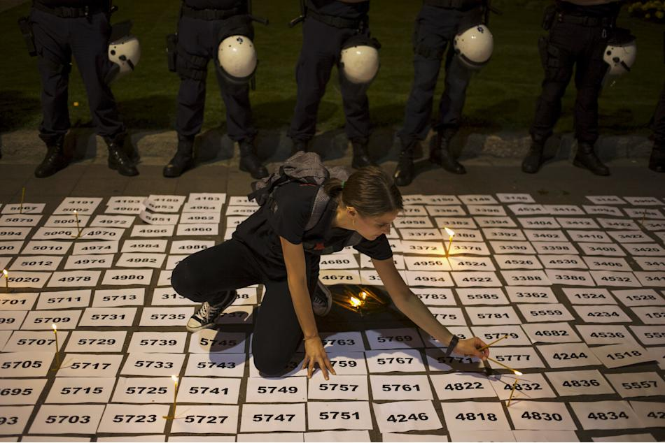 A woman lights candles between papers with numbers symbolizing the victims of the 1995 Srebrenica massacre in downtown Belgrade