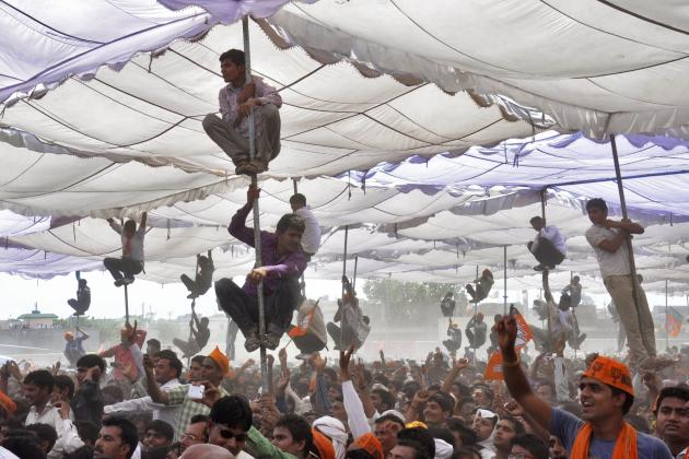 Supporters of Hindu nationalist Modi climb over the poles of a temporary tent to get a glimpse of Modi during an election campaign rally at Mathura