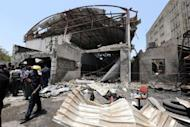 A firefighter stands in front of the office of ThisDay newspaper in Abuja. A suicide attack at the Abuja bureau of a top Nigerian newspaper and an attempted car bombing at another of its offices killed nine people Thursday in the first such strikes on the country's media