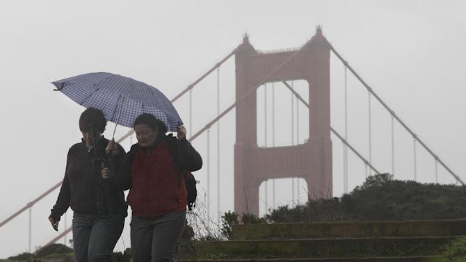 Women walk under an umbrella in front of the Golden Gate Bridge at the Marin Headlands in Marin County, Calif., Thursday, Nov. 29, 2012. The National Weather Service says that by late morning Thursday 1 inch of rain had fallen in several hours across the western side of the county. Much of Northern California is under a variety of warnings and advisories for rain, snow and high winds. (AP Photo/Jeff Chiu)