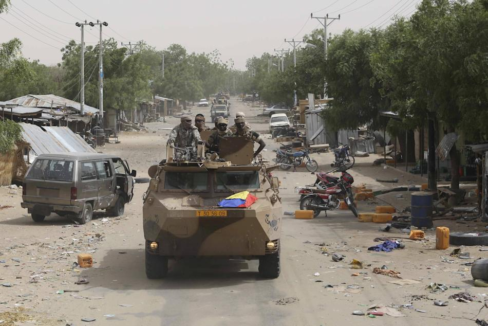 A convoy of soldiers fro, Niger and Chad drive down a looted street in the recently retaken town of Damasak
