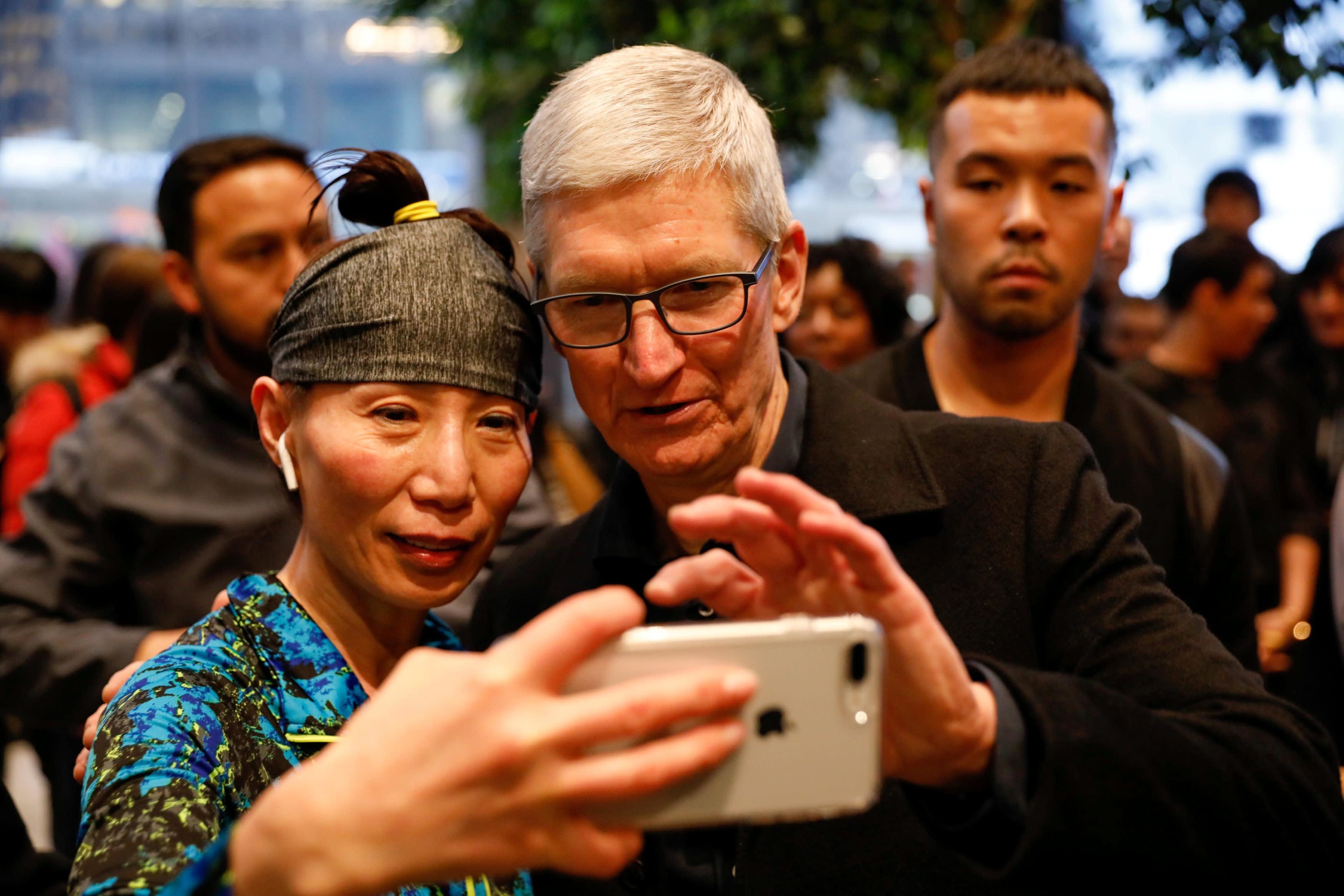 Tim Cook, CEO da Apple, tira uma selfie com um cliente e seu iPhone enquanto visita a Apple Store em Chicago, Illinois, EUA, em 27 de março de 2018. REUTERS / John Gress