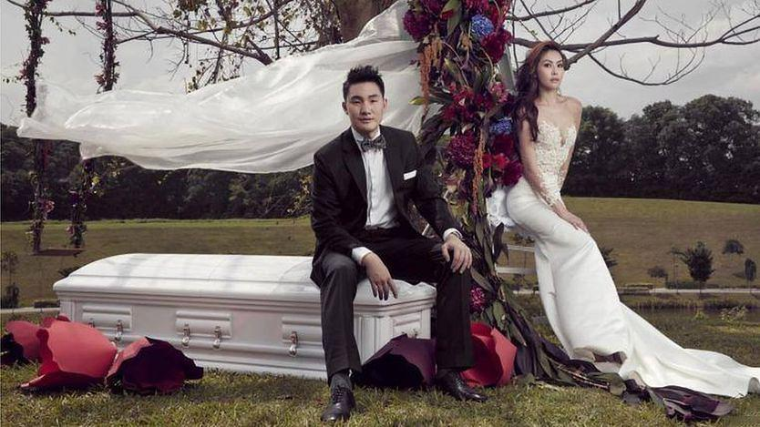 Bride and Groom Pose With Coffin