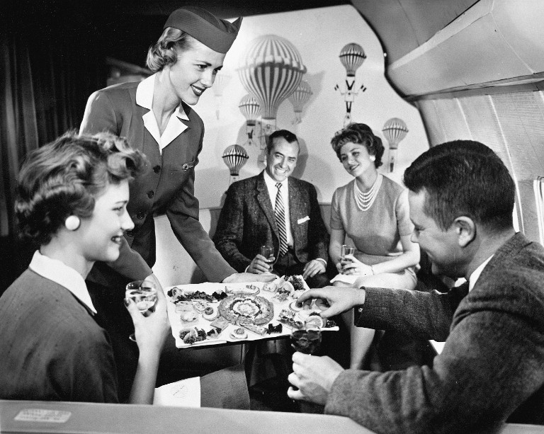A Pan Am stewardess entertains passengers, 1944.