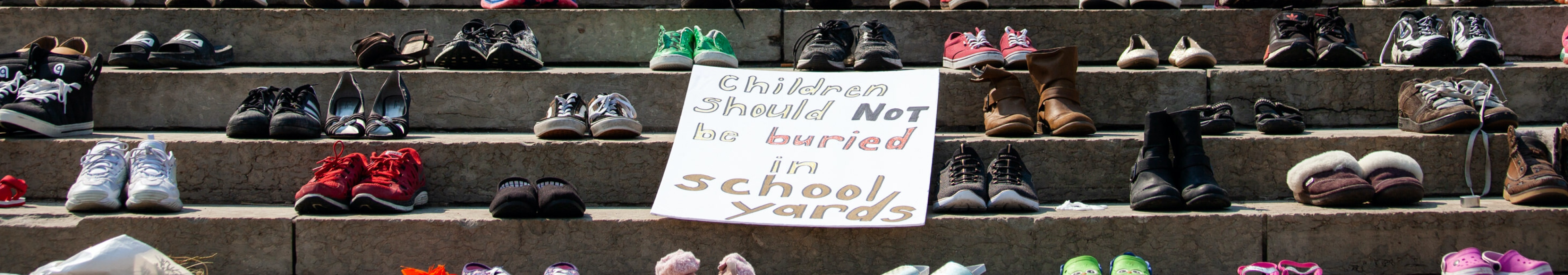 Shoes placed on the steps of the Manitoba Legislature to honour hundreds of children recently discovered in unmarked graves on the sites of several former residential schools across Canada near the now toppled statue of Queen Victoria on July 2, 2021 in Winnipeg, Manitoba, Canada. The statue was pulled down by indigenous protestors following a march to honour survivors and victims of Canadaâs residential school system. (Photo by Daniel Crump/Anadolu Agency via Getty Images)