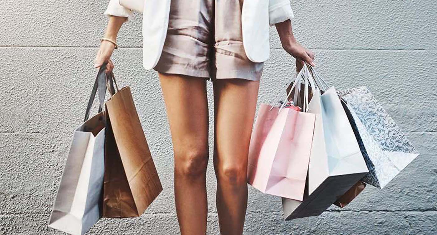 A person with their hands full of shopping bags.