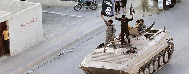 ISIS fighters hold the flag of Islamic State while taking part in a military parade along the streets of northern Raqqa province in this June 30, 2014 file photo. REUTERS/Stringer