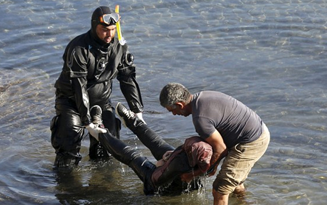 Two men carry a woman's lifeless body from the sea after she drowned off the coast of Lesbos. Source: Reuters.