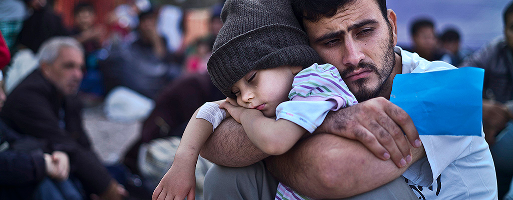 In this Sunday, Oct. 4, 2015 file photo, a Syrian refugee child sleeps in his father's arms while waiting at a resting point to board a bus, after arriving on a dinghy from the Turkish coast to the northeastern Greek island of Lesbos. (AP Photo/Muhammed Muheisen, File)