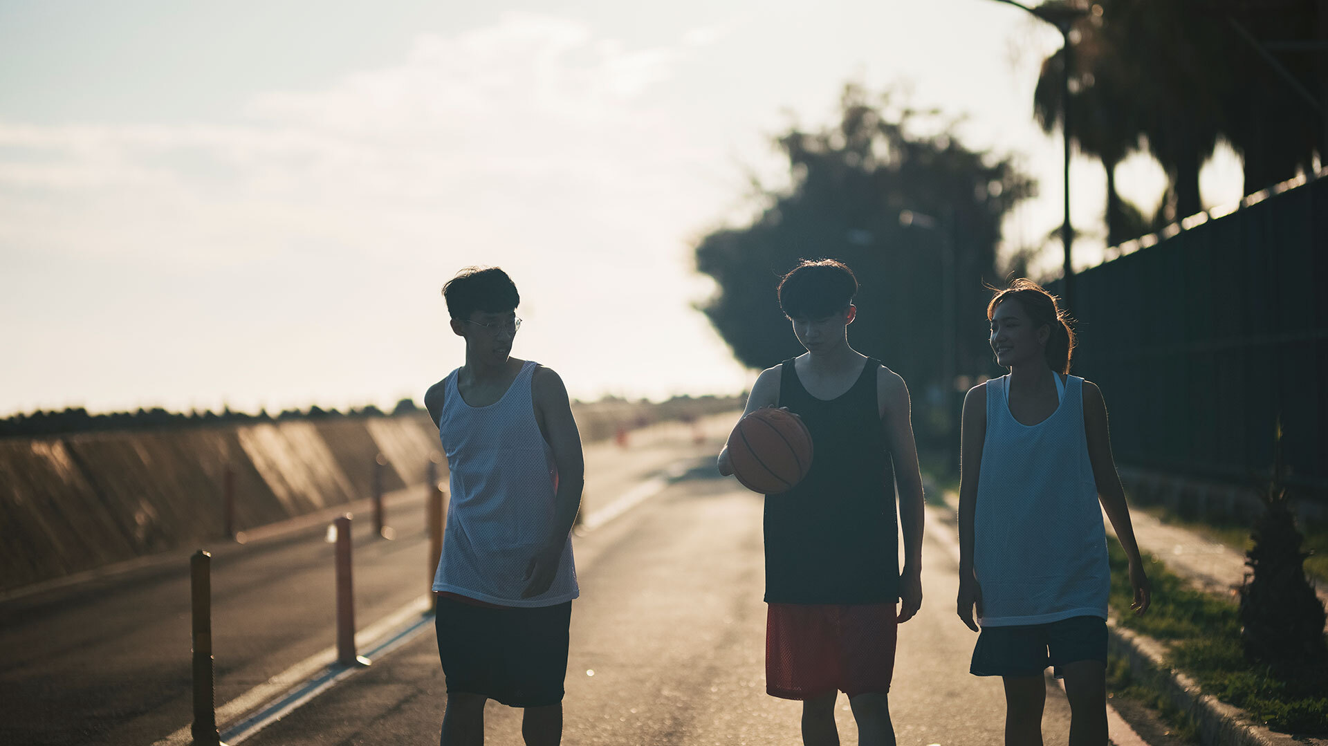 Three youth playing basketball