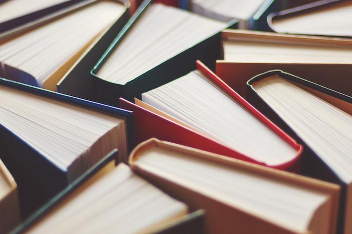 Livros abertos empilhados sobre uma superfície com capas coloridas amarelas, verdes. As folhas do livro são amarelas e não se pode ler seu conteúdo.